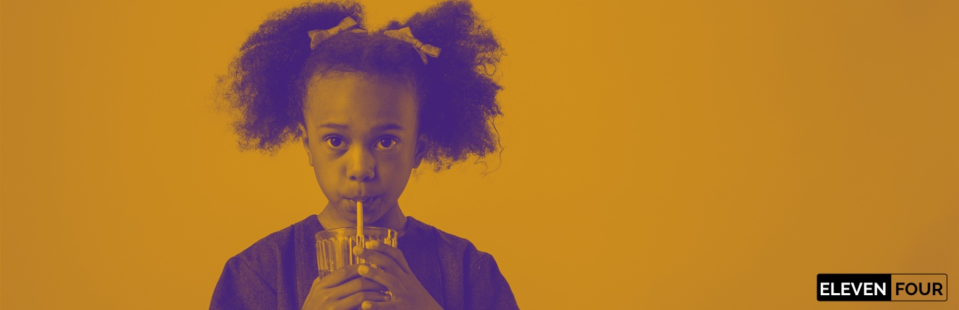 Girl with pigtails drinks using a straw from a glass